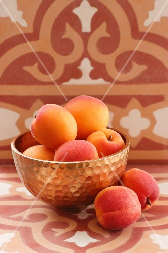 Apricots in a beaten brass bowl in front of a wall decorated with oriental wallpaper