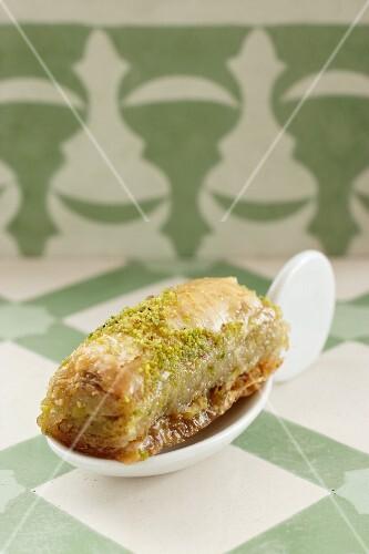 A baklava roll on a canapé spoon