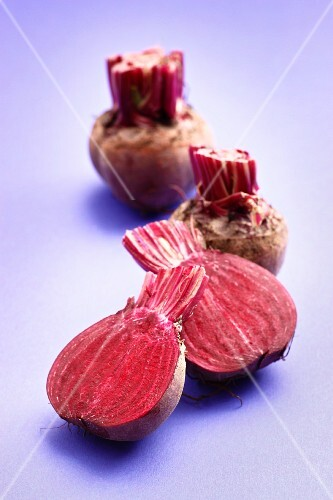 Beetroot, whole and halved, on a purple surface