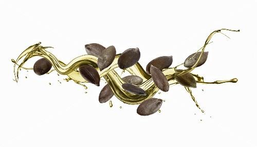 Flying pumpkin seeds in a spiral of pumpkin seed oil