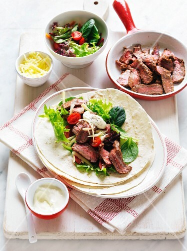 Fajitas with beef, cheese, sour cream and salad
