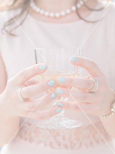 An elegantly dressed young woman holding a glass of white wine