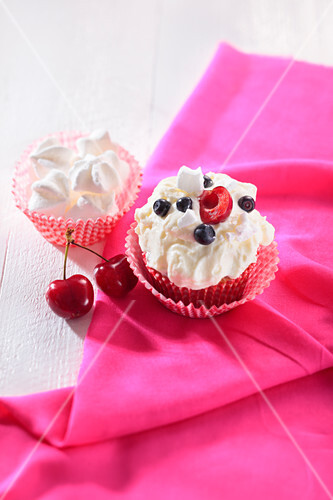 A cupcake topped with meringue, blueberries and cherries