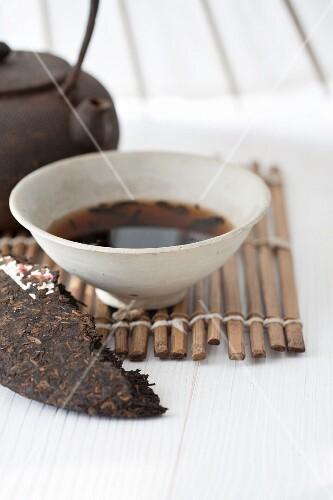 An arrangement featuring a tea brick and brewed pu-ehr tea in a tea bowl