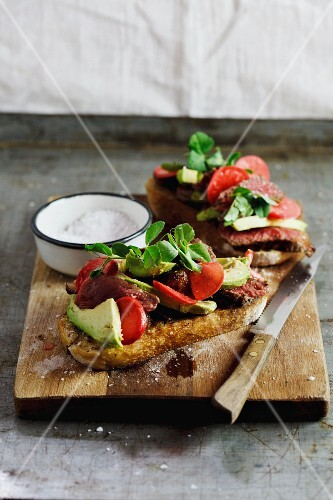 Grilled bread topped with steak, marinated radish and avocado