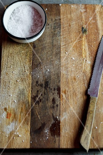 Sea salt and a knife on a wooden board