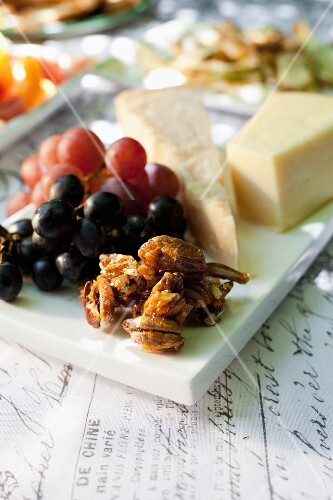 A cheese platter with caramelised pecan nuts and grapes