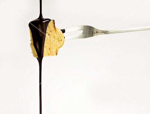 Chocolate being poured over a piece of Baumkuchen (German layer cake)
