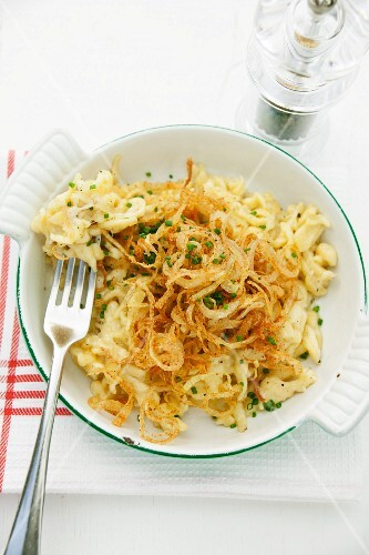 Cheese Spätzle (soft egg noodles from Swabia) with fried onions in an enamel baking dish