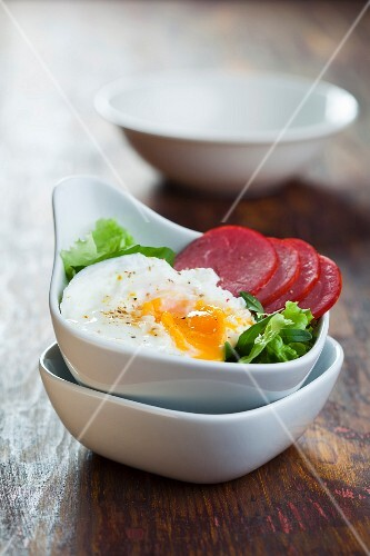 Mixed leaf salad with sausage and poached egg