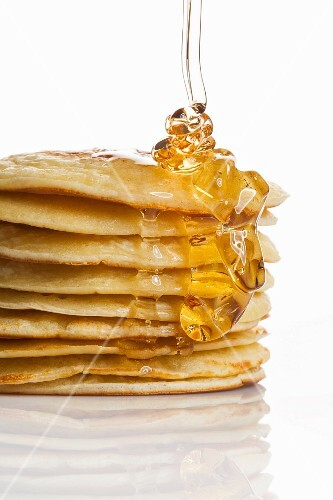 Honey being drizzled onto a stack of pancakes