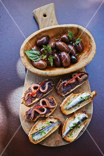 Mediterranean appetiser platter with olives and crostini topped with sardines and anchovies