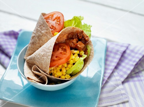 A tortilla wrap with beef, sweetcorn and vegetables