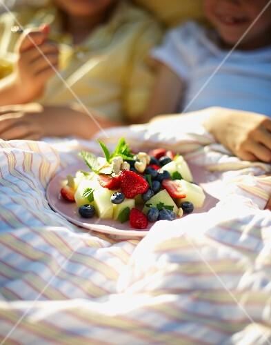 Fruit salad for breakfast in bed in a field