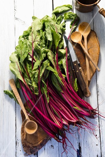 Red chard leaves on a wooden board