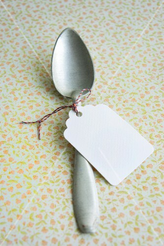 A paper label tied round a silver spoon