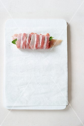 Raw chicken breast with sage wrapped in bacon