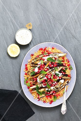 Couscous salad with roasted aubergine, pomegranate seeds and black cumin