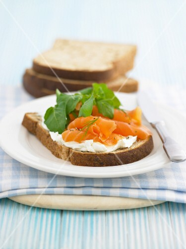 A slice of bread topped with cream cheese and salmon