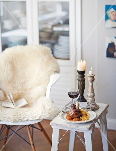 Braised knuckle of lamb oon a side table with a glass of wine and a candlestick