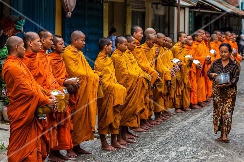 Buddhist monks waiting to receive alms, Battambang, Cambodia