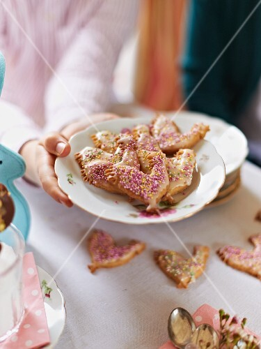 Hands holding a plate of Easter biscuits