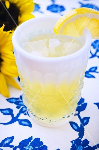 A lemon drink in a thick glass