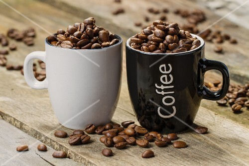 Two cups filled with coffee beans
