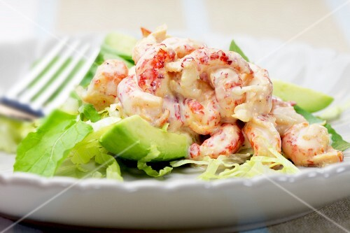 Crayfish with cocktail sauce on a bed of avocado and lettuce