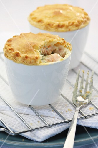 Two mini salmon pies in baking dishes on a wire rack