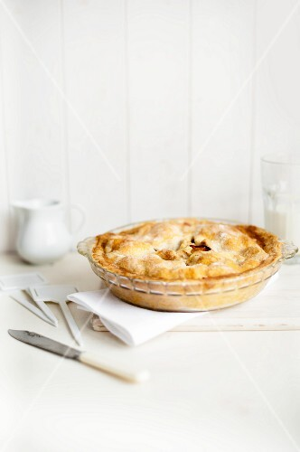 A whole plum pie in a glass dish