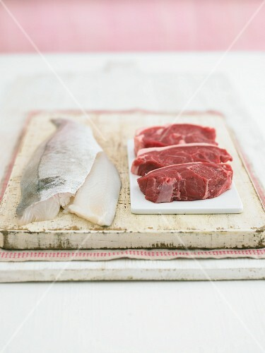 Fish fillets and lamb fillets on a chopping board