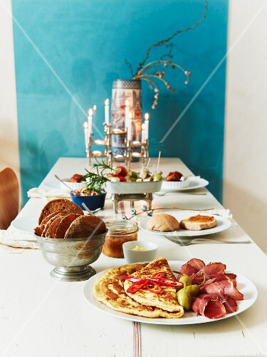 A table laid with pancakes, ham and crispbread