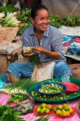 A woman bundling spring onions at a market (Vientiane, Laos)