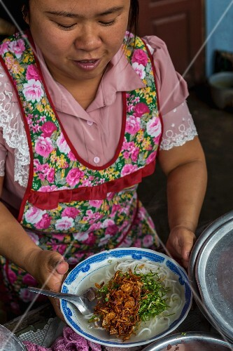 A woman serving noodle soup at a bar (Vientiane, Laos)