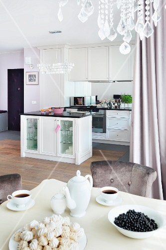 A view from a table laid for afternoon coffee looking towards an elegant, built-in white kitchen with an island counter and crystals from a chandelier at the top of the picture