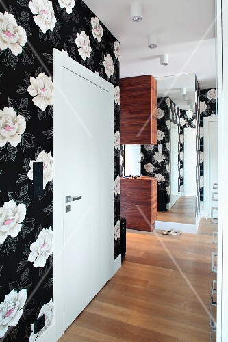 An elegant hallway hung with black and white floral paper with a mirror at the end