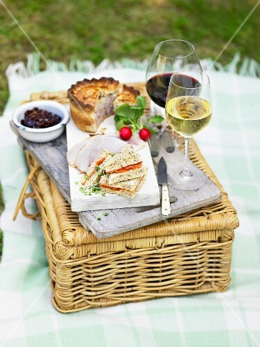 Tramezzini, a meat pie, ham and wine on top picnic basket