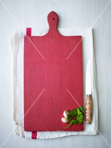 Garlic and parsley on a red wooden chopping board on a tea towel next to a knife