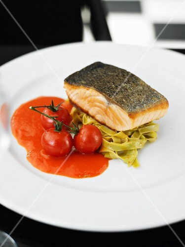 Fried salmon steak on a bed of green tagliatelle with tomato sauce
