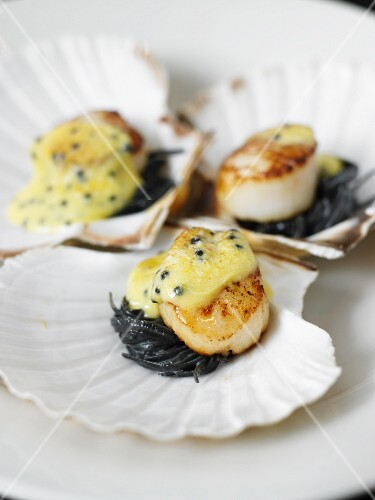 Scallops on black spaghetti topped with melted cheese
