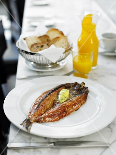Smoked herring with herb butter with white bread and orange juice in the background
