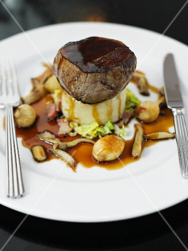 A beef medallion on a bed of mashed potatoes and parsnips with gravy and shallots