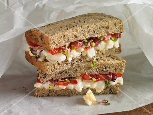 Egg, tomato and cress sandwich on brown bread wrapped in greaseproof paper