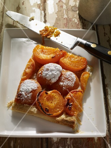 A slice of apricot and almond tart on a plate