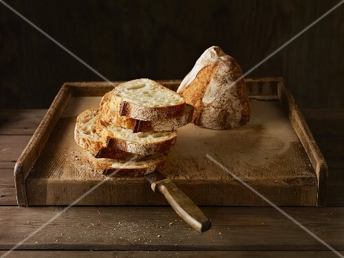 A halved loaf of artisan bread, half sliced, on a wooden board