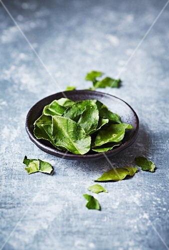 Dried kaffir lime leaves on a small plate