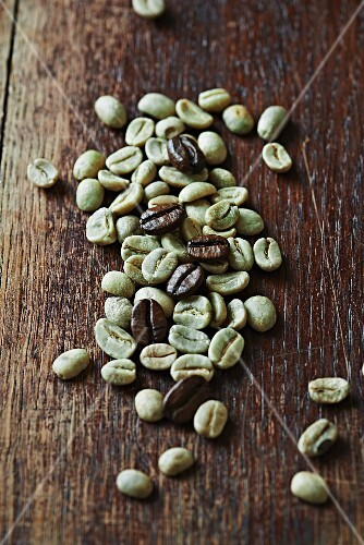 Green and roasted organic coffee beans on wooden surface