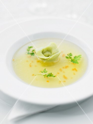 A clear broth garnished with a tortellino and chervil