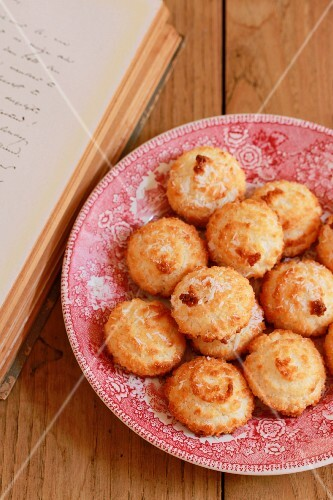Coconut macaroons on a plate next to a book